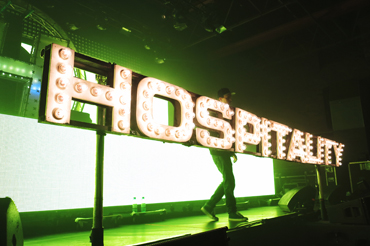 Hospitality light bulb sign at the front of the stage