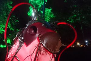 Close up of Heart of the Forest sculpture lit up at night amongst trees.