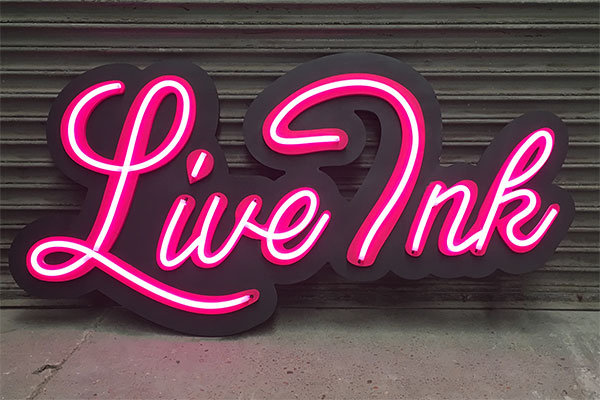 Pink LED neon sign in cursive script, Live Ink